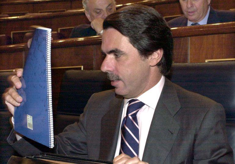 El presidente del Gobierno, José María Aznar, saca de la cartera su cuaderno azul antes del comienzo de la sesión del Debate sobre el estado de la Nación el 27 de junio de 2001.