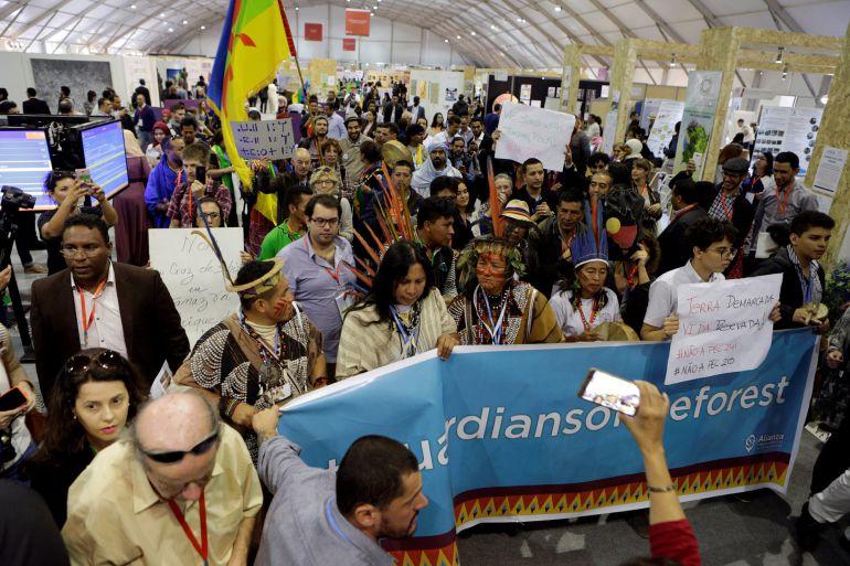 Un grupo internacional de representantes de pueblos indígenas se manifiesta en el interior de la Cumbre del Clima de Marrakech (COP22) para exigir a las potencias industriales que reduzcan drásticamente sus emisiones de C02 para frenar el cambio climático.