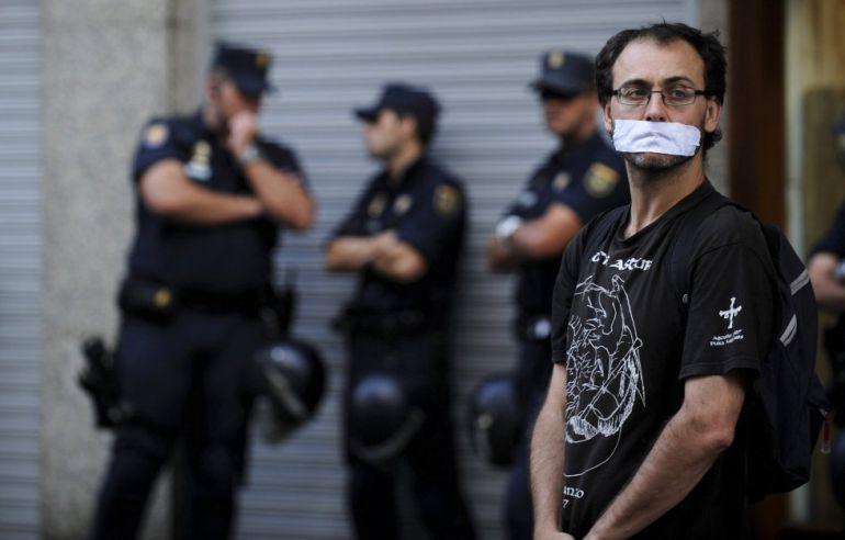 Un hombre con la boca tapada y rodeado de policía durante una manifestación contra la 'Ley Mordaza' en Gijón.
