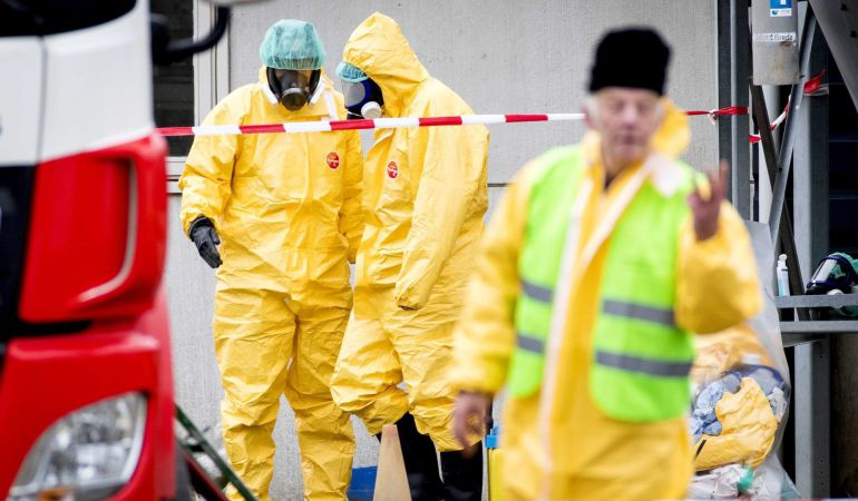 Empleados de la Sanidad con máscaras protectivas están evacuando una granja de patos tras detectarles la gripe aviar en Biddinghuizen, Holanda.