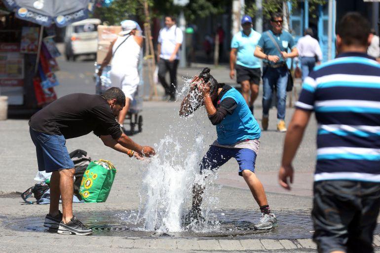 Un grupo de personas se refrescan en las calles de Santiago de Chile que está registrando estos días una serie de de temperaturas extremas.