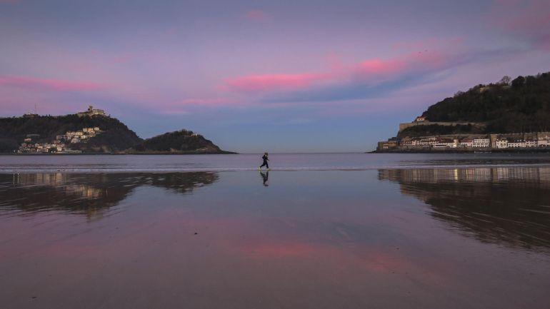 Dos personas corren al amanecer por la orilla de la playa de La Concha de San Sebastián.