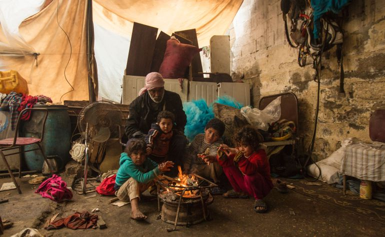 Niños alrededor del fuego en un campo de refugiados de Gaza
