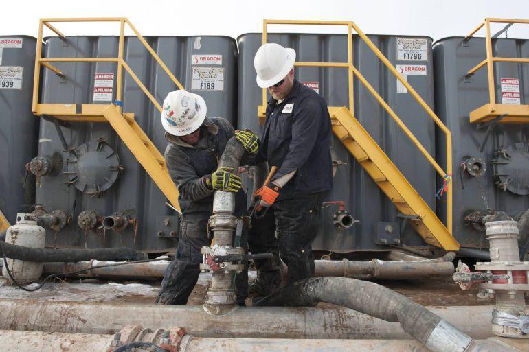 """Dos operarios trabajan en una planta que utiliza el método de extracción de gas mediante el """"fracking"""" o técnica de fracturación hidráulica."""