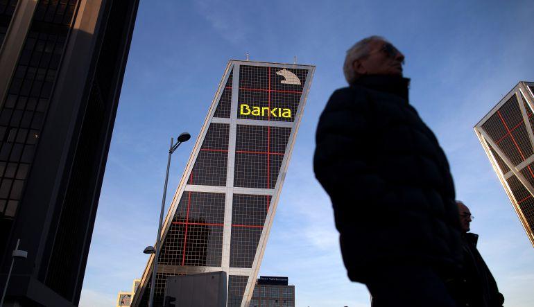 Ciudadanos caminan ante las oficinas centrales de Bankia en Madrid