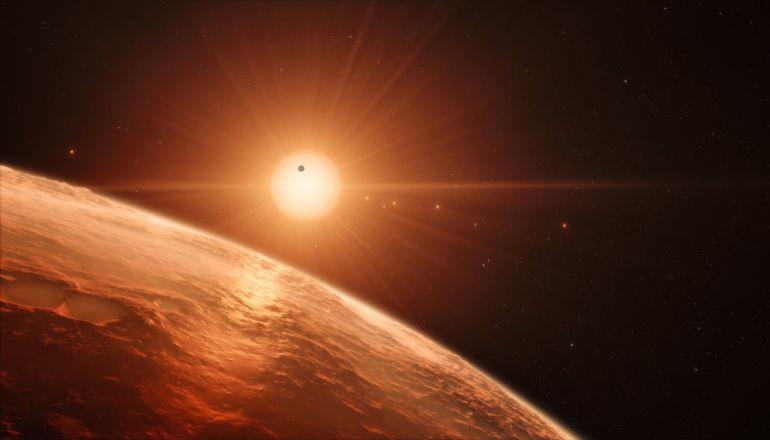 Recreación artística desde la superficie de uno de los exoplanetas del sistema TRAPPIST-1, un sistema de siete planetas que orbitan esta estrella enana ultrafría situada a una distancia de sólo 40 años luz de la Tierra .