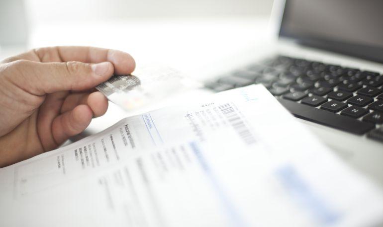 Un empleado comprueba documentos bancarios y una tarjeta en una oficina