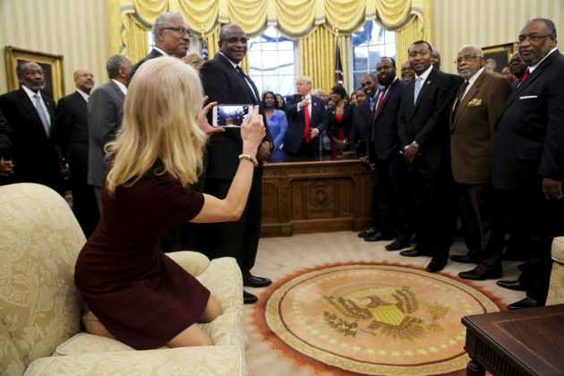 Kellyanne Conway (i), toma una fotografía arrodillada en el sofá.