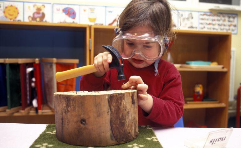 Una niña trabaja con la madera en una escuela Montessori.
