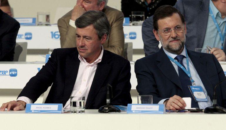 El presidente del PP, Mariano Rajoy (d), conversa con el entonces secretario general saliente del partido, Ángel Acebes (i), durante el XVI Congreso Nacional del PP que se celebró en la Feria de Muestras de Valencia.