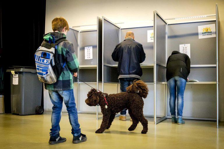 Varias personas acuden a un colegio electoral para ejercer su derecho al voto durante las elecciones parlamentarias en La Haya (Holanda).