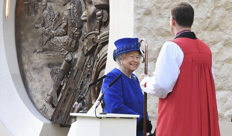 La reina Isabel II conversa con un clérigo.