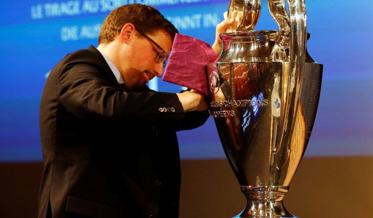 Un empleado de la UEFA le da lustre al trofeo antes del sorteo