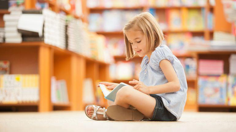 Una niña disfruta con la lectura en una librería.