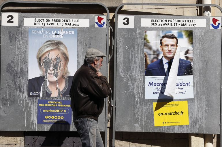 Un ciudadano camina ante los carteles de campaña de Marine Le Pen y  Emmanuel Macron en París