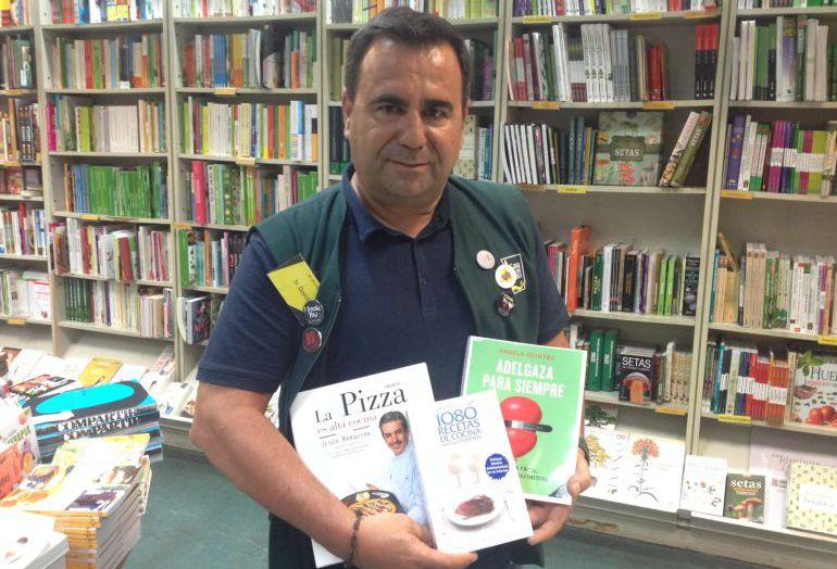 David García, de la sección de Gastronomía de la casa del Libro, posando con el libro más vendido, el que más se está vendiendo y el que más se va a vender.