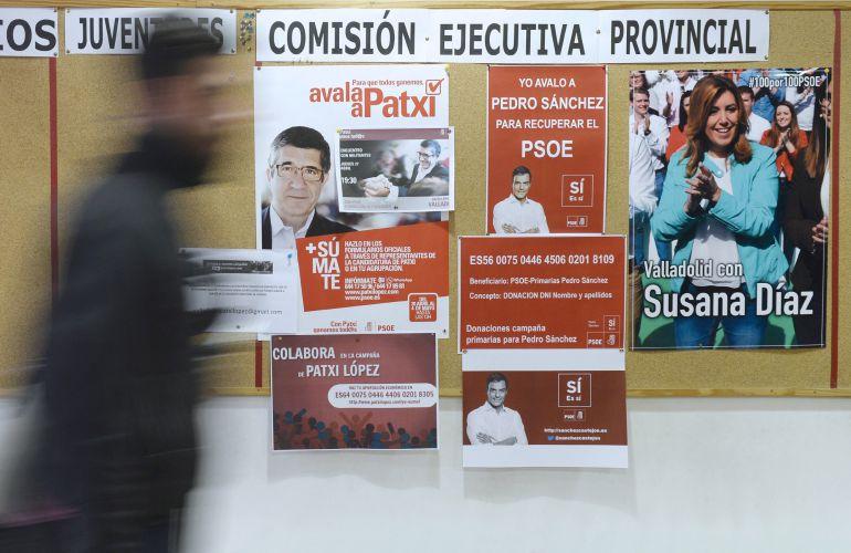 Un hombre pasa por delante de los carteles de apoyo a los tres candidatos a la Secretaría General del PSOE