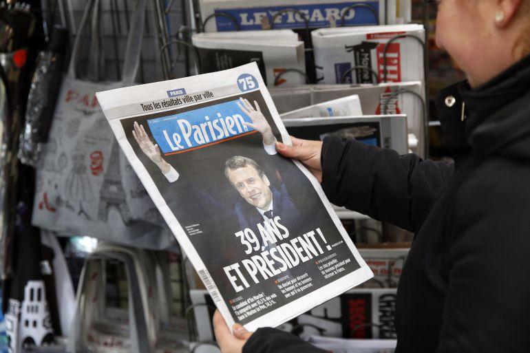 Una mujer mira la portada de 'Le Parisien' con la foto de Macron como ganador de las presidenciales en Francia