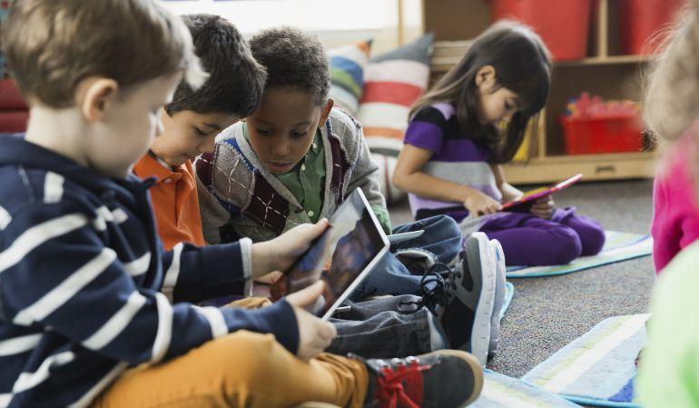 Varios niños utilizando unas tabletas.