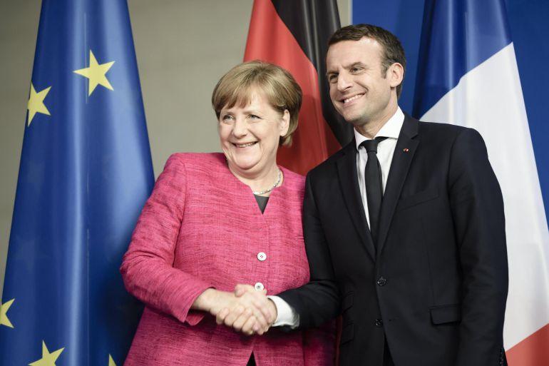 La canciller alemana Angela Merkel (i) y el presidente francés Emmanuel Macron (d) antes de la rueda de prensa tras su encuentro en la cancillería alemana en Berlín