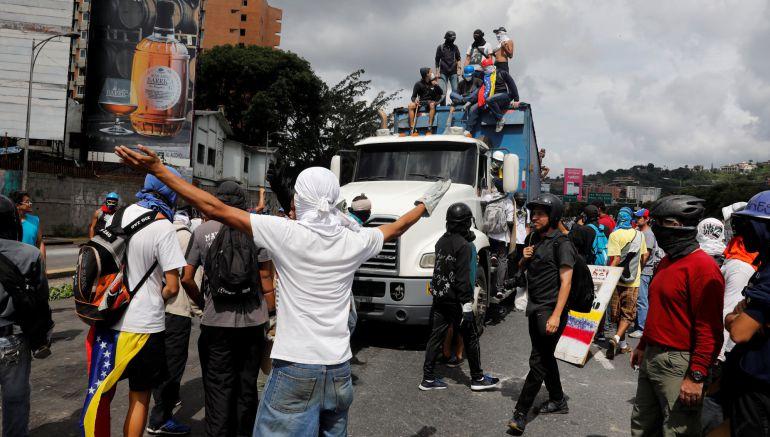 Manifestantes bloquean a un camión durante las protestas en Caracas
