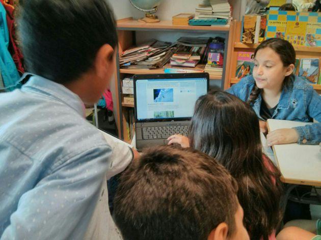 Un grupo busca información en el ordenador.