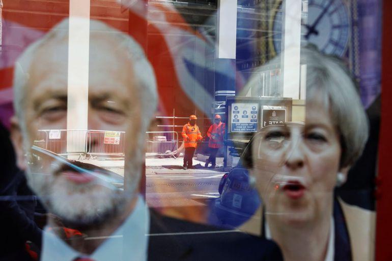 Trabajadores reflejados en una ventana sobre los carteles electorales de Theresa May y Jeremy Corbyn