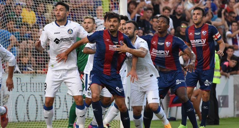 Los jugadores del Huescan intentan rematar un córner en área rival