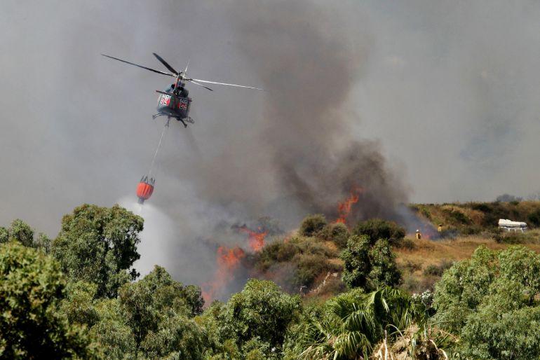 Un helicóptero echa agua en un incendio forestal que se ha  registrado en la provincia de Cádiz y que ha obligado a desalojar varias viviendas.