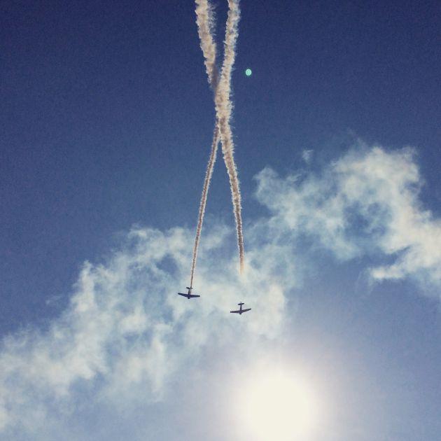 Dos aviones hacen piruetas mientras sobrevuelan el cielo.
