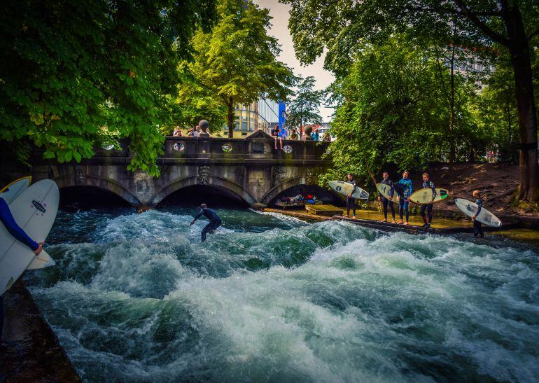 Surfistas disfrutan de las olas en el centro de Munich.