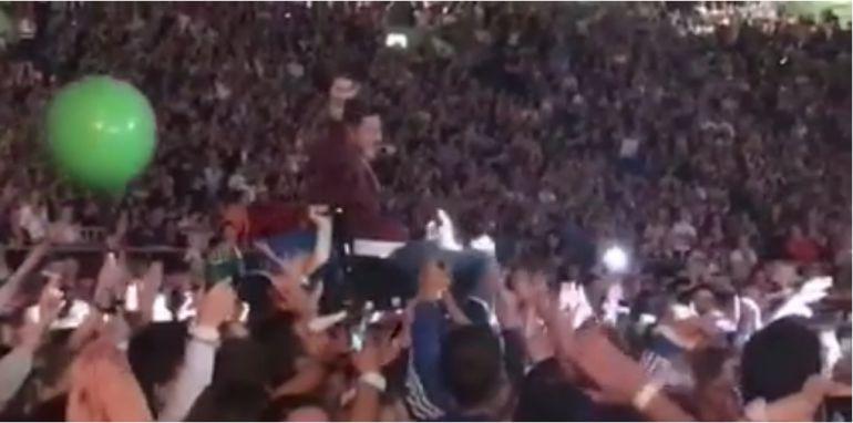 Un fan de Coldplay en silla de ruedas es aupado entre la multitud y acaba tocando en directo