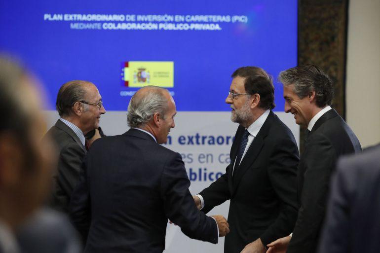 El presidente del Gobierno, Mariano Rajoy (2d), y el ministro de Fomento, Íñigo de la Serna (d), a su llegada a la presentación del Plan Extraordinario de Inversiones en Carreteras.