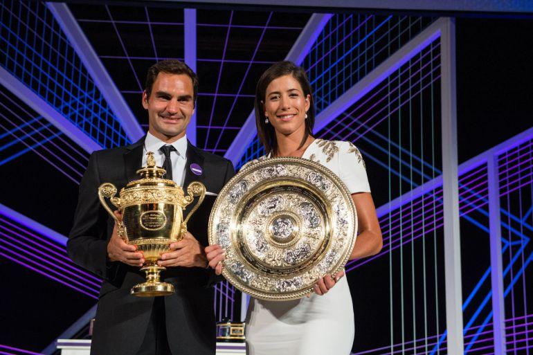 Muguruza posa junto a Federer mientras ambos sostienen sus trofeos de Wimbledon
