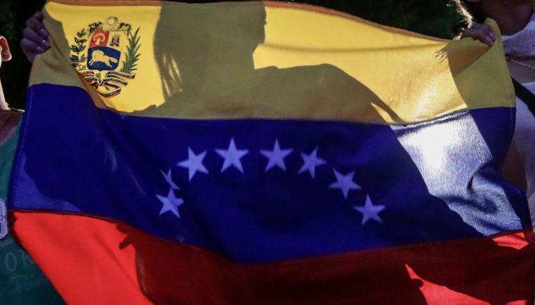 Bandera venezolana durante una concentración al cierre de las votaciones de la consulta impulsada por la oposición sobre la Constituyente.