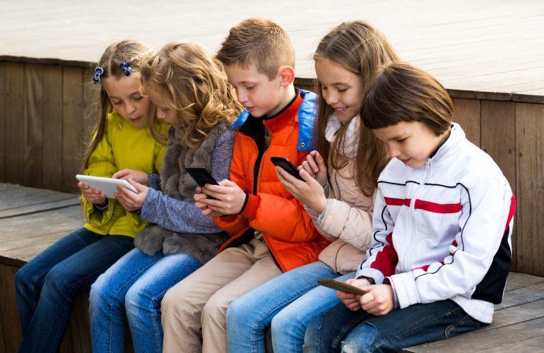 Un grupo de chicos utiliza tabletas y teléfonos móviles.