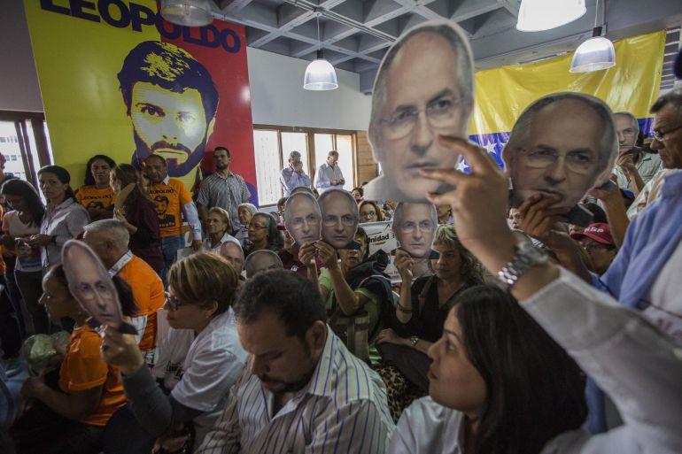 Un grupo de personas con afiches alusivos a leopoldo López y Antonio Ledezma asisten a una rueda de prensa de los partidos políticos Voluntad Popular y Alianza Bravo Pueblo