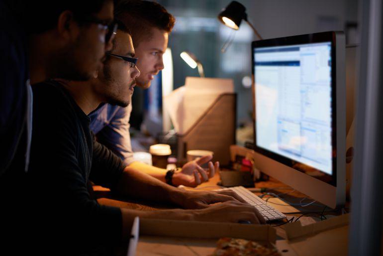 Expertos informáticos frente a un ordenador en su puesto de trabajo