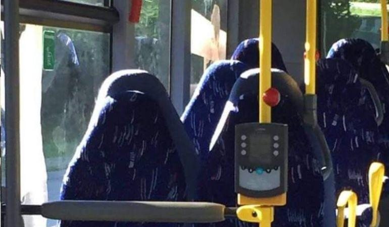Fotografía de los asientos vacíos de un autobús que fueron confundidos con seis mujeres con burka por un grupo racista de Facebook.