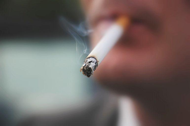 Primer plano de un joven fumando un cigarrillo