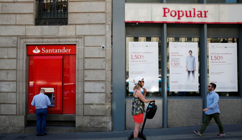 A man uses a cash dispenser at a branch of Spain's biggest bank Santander next to a Banco Popular branch in Madrid
