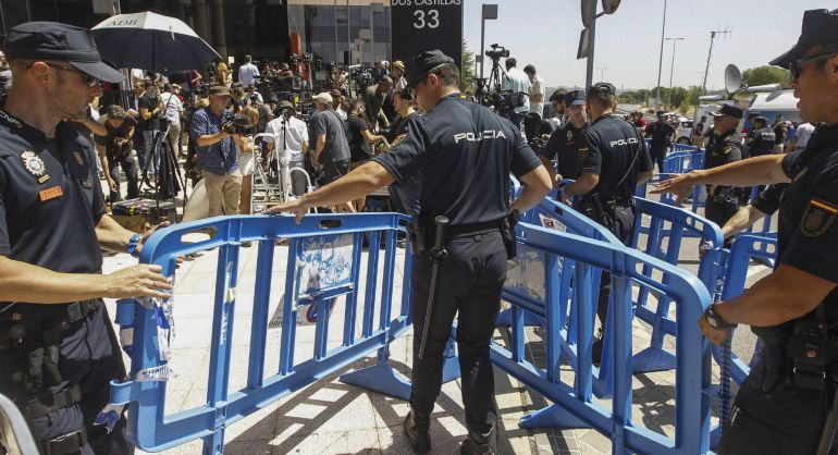 Agentes de Policía Nacional junto a la barrera que separa a los medios de comunicación que esperaban la salida del delantero del Real Madrid Cristiano Ronaldo