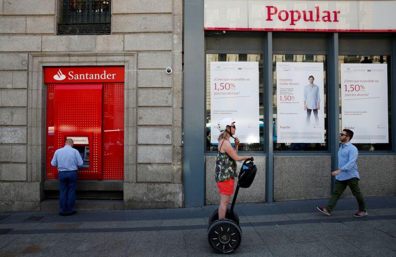 Un cajero del Banco Santander junto a una oficina del Popular.