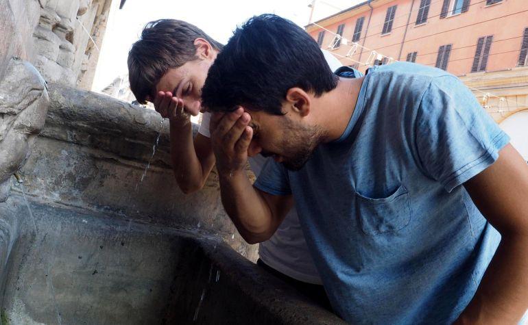 Dos chicos mojan su cara en una fuente para combatir las altas temperaturas