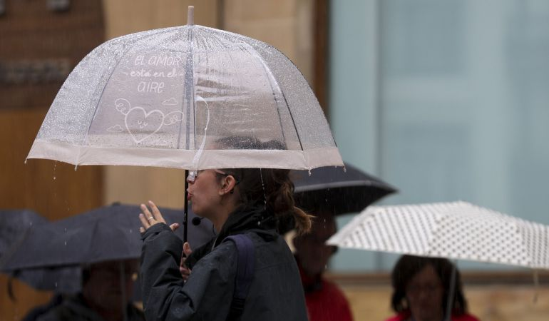 Un grupo de turistas se protege con paraguas de las incesantes lluvias que se registran en San Sebastián, la capital guipuzcoana.