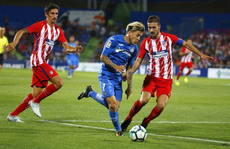 El capitán del Atlético de Madrid, Gabi Fernández, lucha el balón con Álvaro, del Getafe.