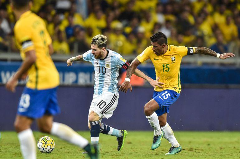 Messi y Paulinho se disputan el balón durante un partido de las selecciones