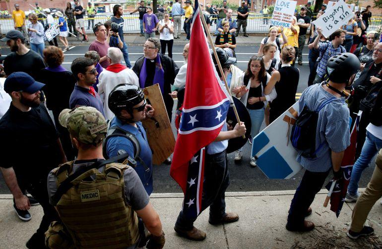 Un supremacista blanco cargando con una bandera confederada momentos antes de la manifestación convocada en Charlottesville, Virginia.