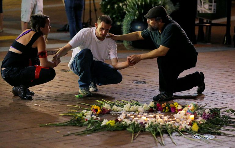 Dos personas rinden homenajes a uno de los fallecidos.