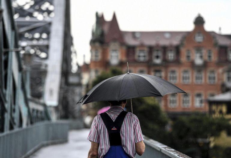 Un hombre cruza el puente de Loschwitz durante un día lluvioso Dresden